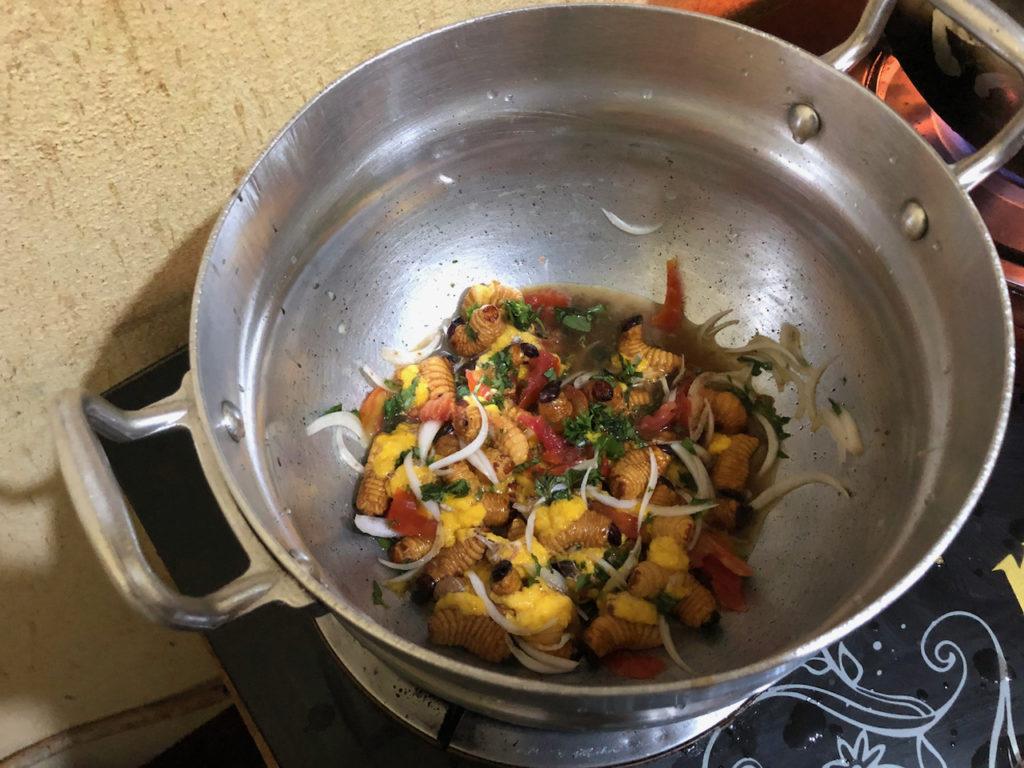 Préparation en cuisine avec herbes, oignons et tomates